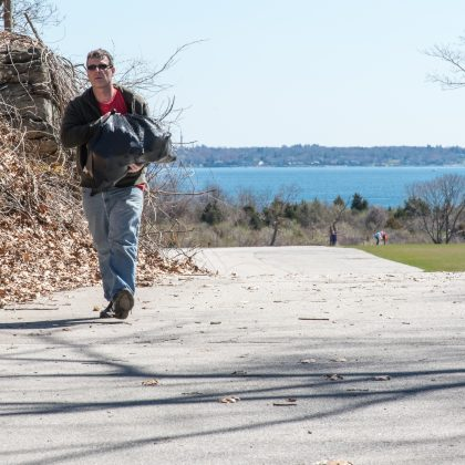 Man Carrying bag of trash at Bay Rocky